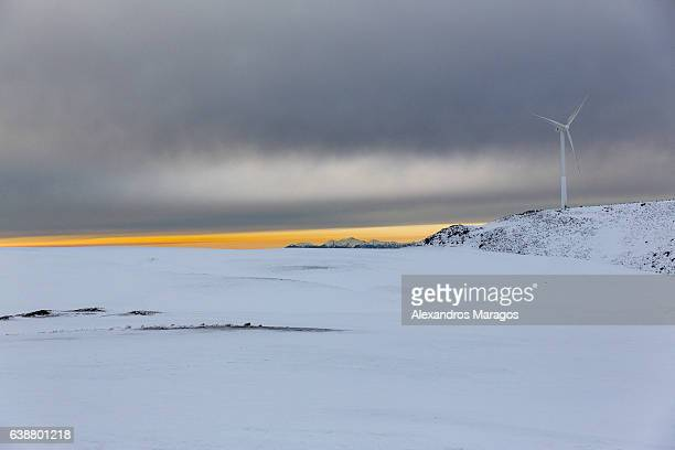 Wind Turbine in snow-covered mountain at Sunset