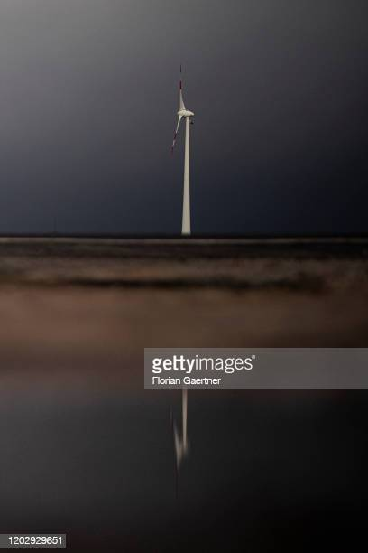 A wind turbine is pictured in front of dark clouds on February 18 2020 in Bredow Germany