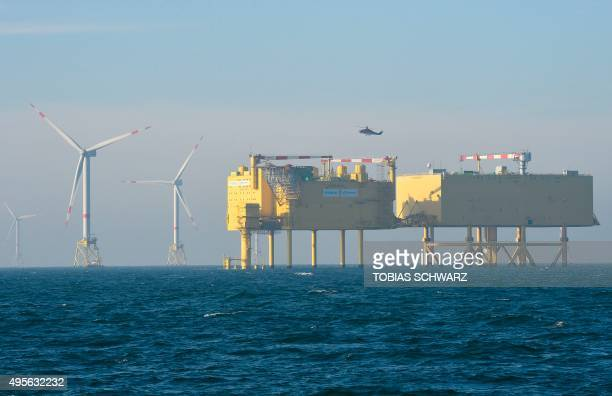 A wind turbine is pictured next to an electrical offshore substation operated by European electricity transmission system operator TenneT near the...