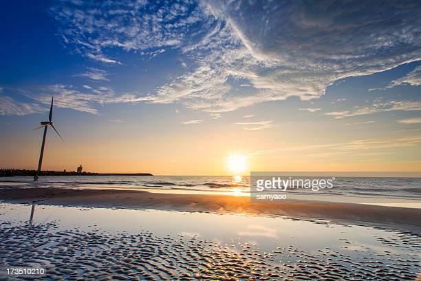 Wind turbine on beach during sunset