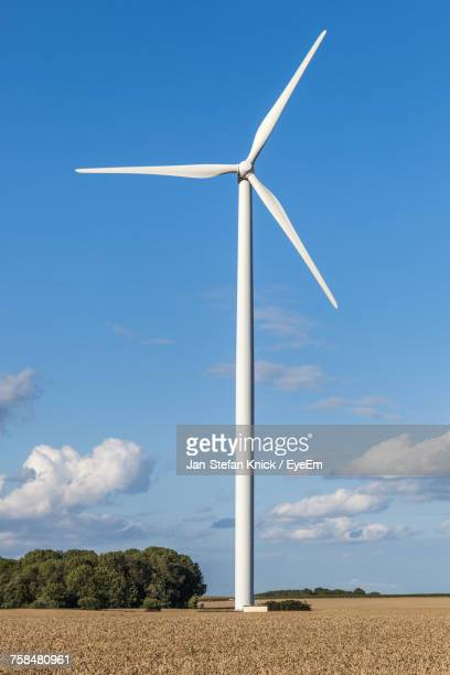 wind turbine on field against blue sky - mill stock pictures, royalty-free photos & images