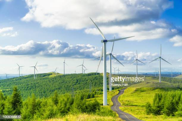 wind turbine on field in hill - windenergie stockfoto's en -beelden