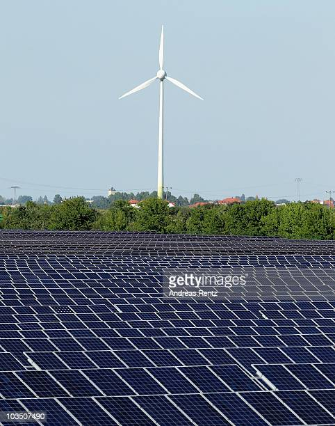 A wind turbine spins behind a field of solar cell panels on August 20 2010 in Roedgen near Bitterfeld Germany Germany is investing heavily in...