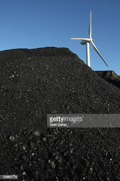 A wind turbine stands behind a mound of coal outside a factory August 3 2007 in Buettel Germany Energy has become one of the most heated topics of...