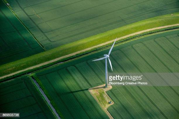 a wind turbine stands in a field of agricultural crops - energieindustrie stock-fotos und bilder