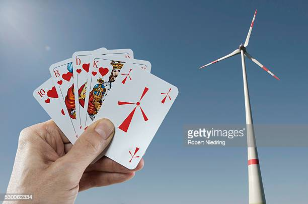 Wind turbine with a man's hand holding playing cards in foreground, Bavaria, Germany