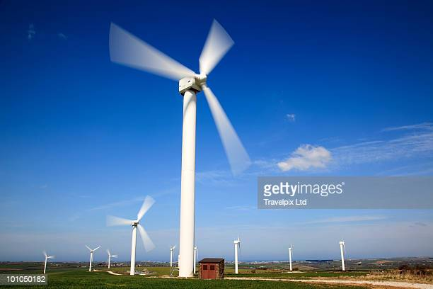 wind turbines against blue sky - spinning stock pictures, royalty-free photos & images