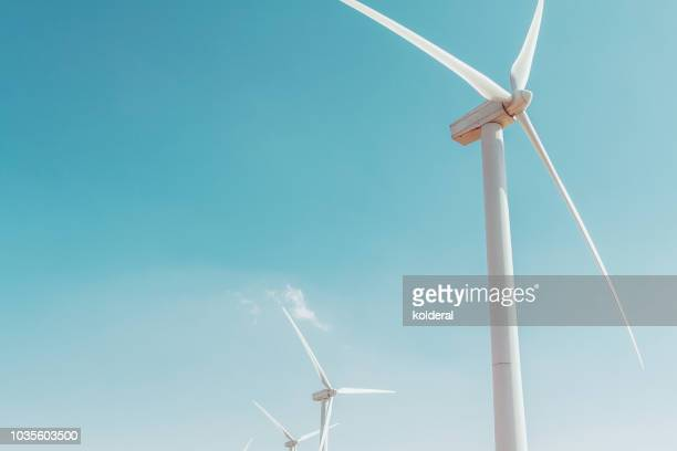 wind turbines against blue sky - energy efficient stock photos and pictures