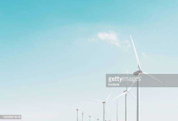 wind turbines against blue sky - windmills stock photos and pictures
