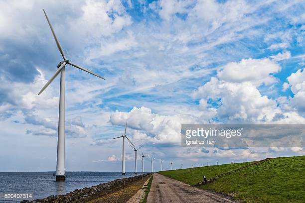 wind turbines along a dyke - ignatius tan stock photos and pictures