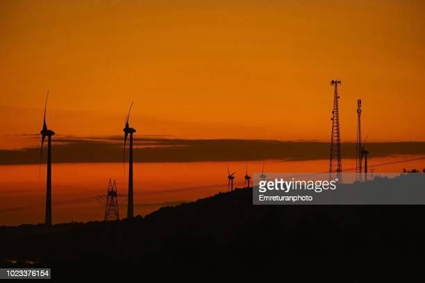 wind turbines and electric lines at sunset. - emreturanphoto stockfoto's en -beelden