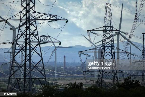 Wind turbines and electricity pylons dominate the landscape at Ince Salt Marshes near to chemical and manufacturing plants on the River Mersey...