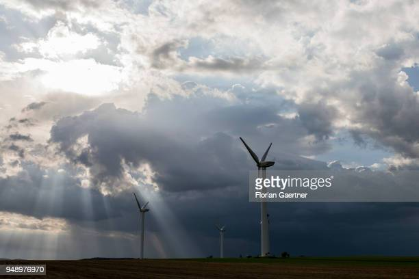 Wind turbines are pictured in front of dark clouds and the shining sun on April 13 2018 in Melaune Deutschland