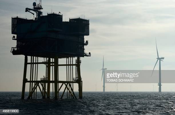 Wind turbines are pictured next to an electrical offshore substation operated by Germany's biggest power supplier Eon at the offshore wind farm...