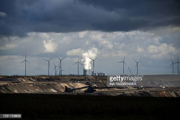 Wind turbines are seen near the open-cast mining and the coal-fired power station Neurath of German energy giant RWE in Garzweiler, western Germany,...