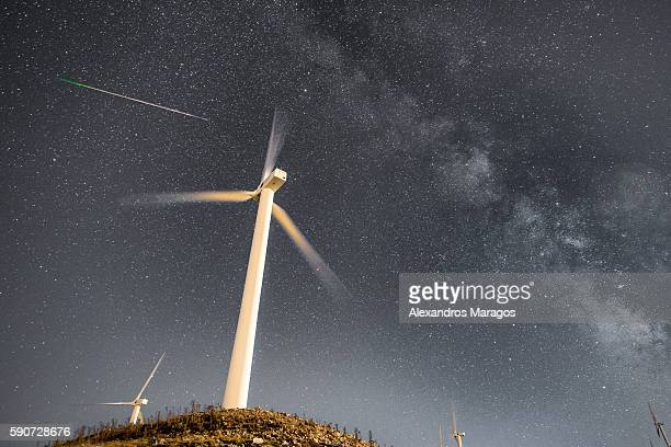 Wind Turbines at night with the Milky Way and a meteor