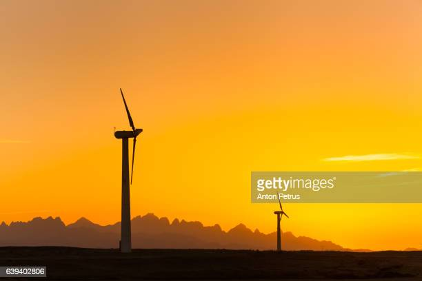 Wind turbines at sunset sky background