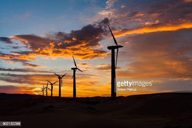wind turbines at sunset sky background - carbon footprint stock pictures, royalty-free photos & images