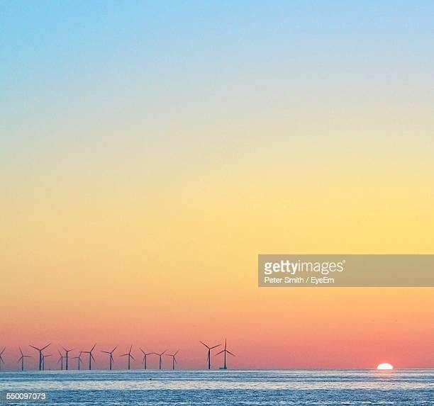 Wind Turbines By Sea Against Clear Sky During Sunset
