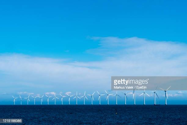 wind turbines by sea against sky - denmark stock pictures, royalty-free photos & images