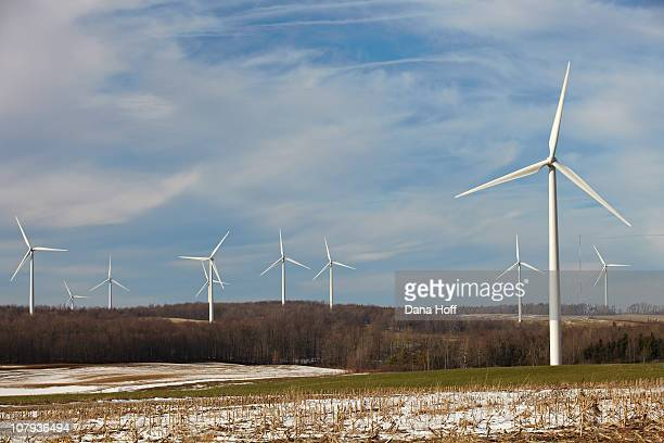 Wind turbines create electricity on sunny day