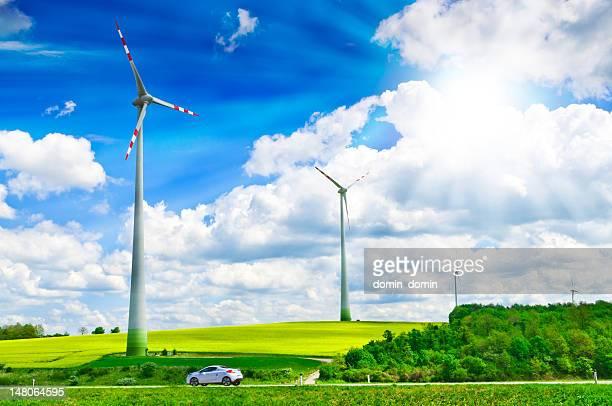 Wind turbines farm on rape field, modern ecology car, sky