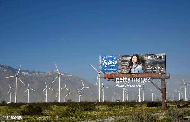 Wind turbines generate electricity at the San Gorgonio Pass Wind Farm near Palm Springs, California, adjacent to a billboard advertising California...