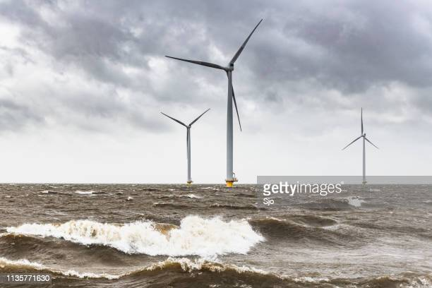 wind turbines in an offshore wind park during a storm with big waves hitting the shore - climate stock pictures, royalty-free photos & images