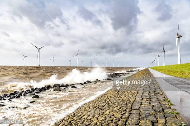 大きな波が岸に当たる嵐の間の洋上風力発電場の風力タービン