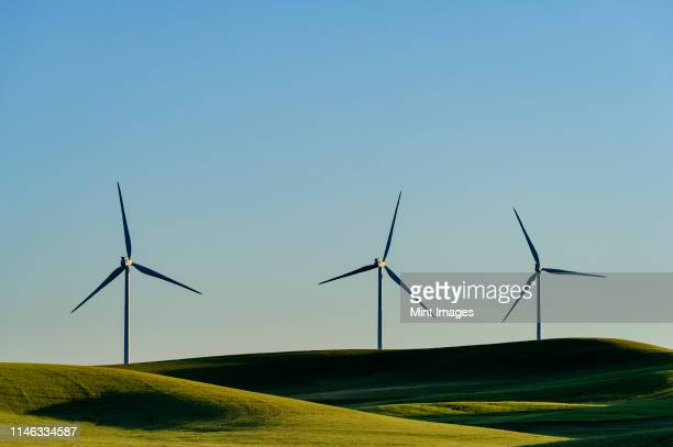 wind turbines in green rolling landscape - wind power stock pictures, royalty-free photos & images