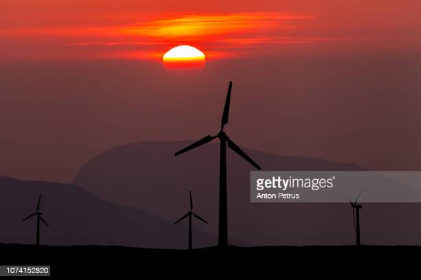 Wind turbines in mountains at sunset sky background