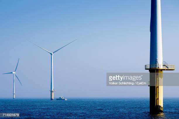Wind Turbines In Sea Against Clear Sky
