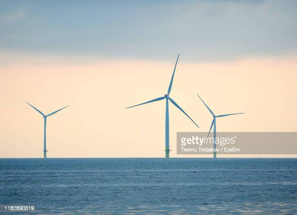 wind turbines in sea against sky during sunset - teemu tretjakov stock pictures, royalty-free photos & images
