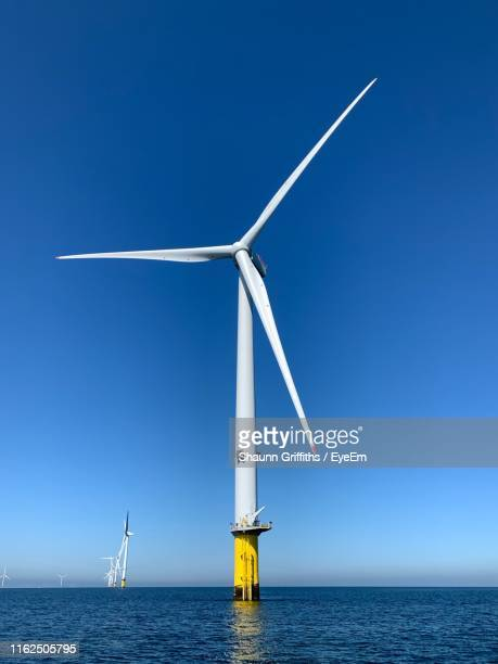 wind turbines in sea against sky - sea stock pictures, royalty-free photos & images