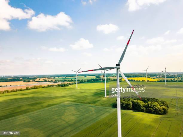 wind turbines in sunny landscape - climate stock pictures, royalty-free photos & images