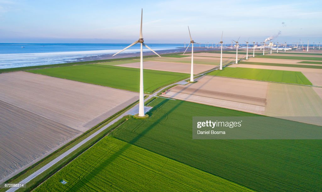 Wind turbines lined up along coast towards industrial area : Stock Photo