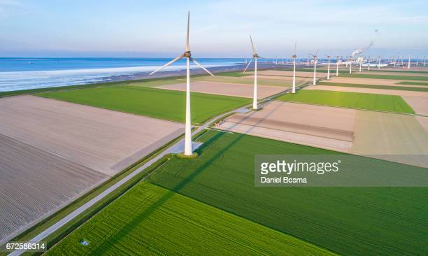 Wind turbines lined up along coast towards industrial area