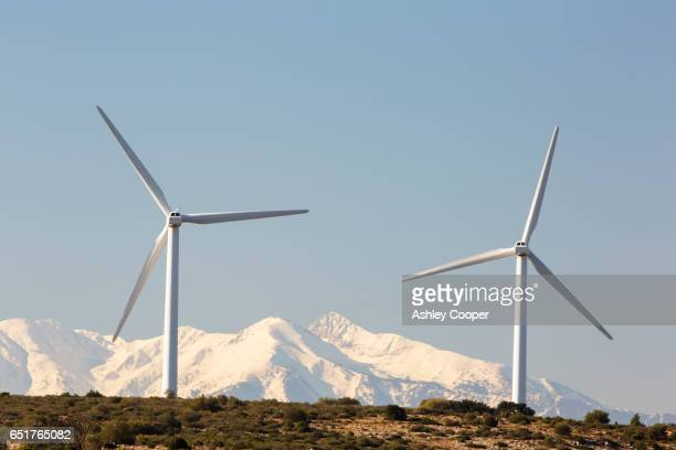 Wind turbines near Opoul in the South of France with the snow covered Pyranean mountains behind.