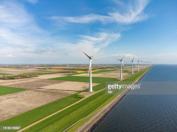 """wind turbines on a levee with agricultural fields and a lake in the background. - """"sjoerd van der wal"""" or """"sjo"""" stock pictures, royalty-free photos & images"""