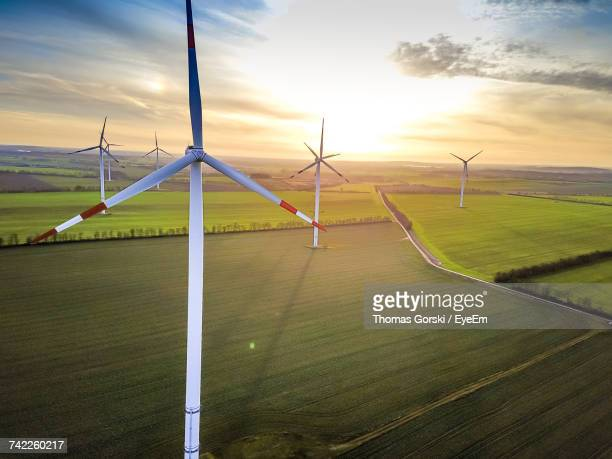 wind turbines on grassy field during sunrise against cloudy sky - strom stock-fotos und bilder