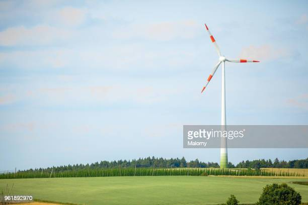 wind turbines on green fields against blue sky. - klima stock-fotos und bilder