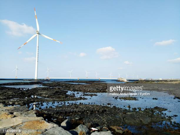 wind turbines on land against sky - jeju stock photos and pictures