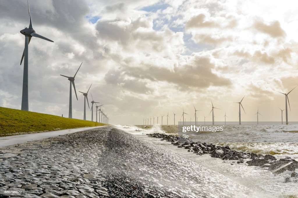 Windturbines op land en offshore in een storm : Stockfoto