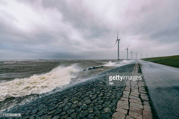 wind turbines on land and offshore in a storm with waves hitting a levee - storm stock pictures, royalty-free photos & images