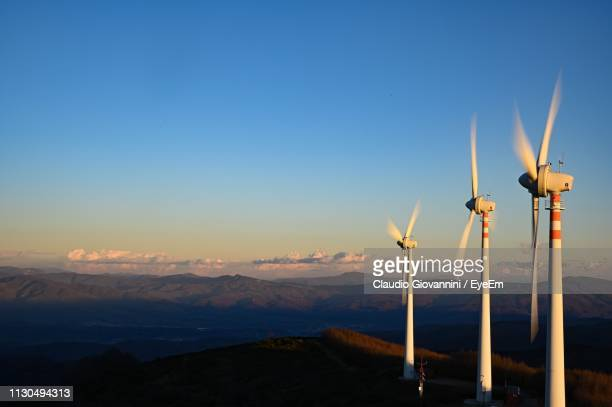Wind Turbines On Landscape Against Sky During Sunset