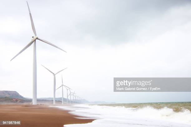Wind Turbines On Shore At Beach Against Sky