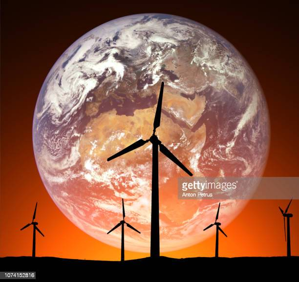 Wind turbines on the background of the planet Earth. Concept of renewable energy