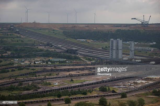Wind turbines operate beyond conveyor belts at an open pit lignite mine also known as brown coal operated by RWE AG in Hambach Germany on Monday 7...