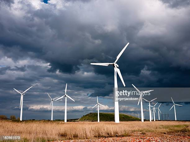 wind turbines photographed against a dark, stormy sky - denmark stock pictures, royalty-free photos & images
