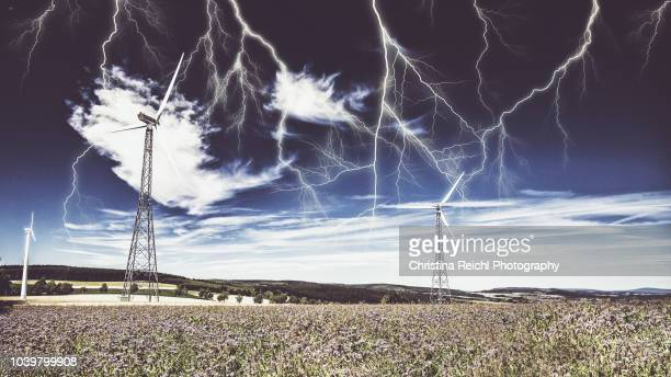 wind turbines producing electricity while lots of lightning bolts hit them - christina luft stock-fotos und bilder